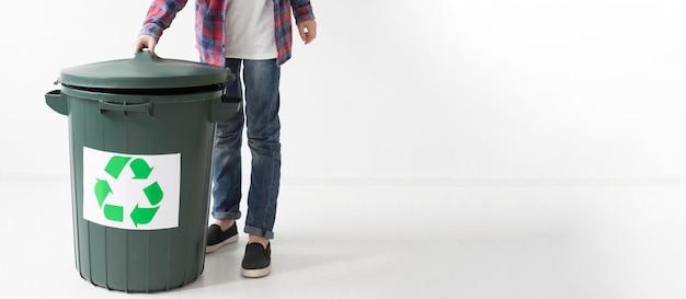 Chico joven y papelera de reciclaje con espacio de copia