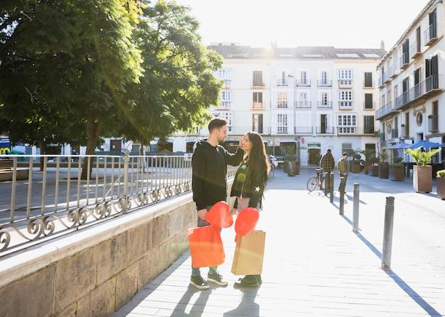 Chico joven con paquetes y globos cerca de ady en la calle