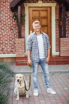 Chico joven con perro perdiguero caminando cerca de la casa