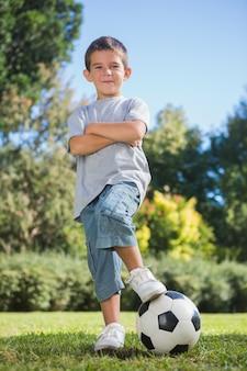Chico joven posando con fútbol con los brazos cruzados