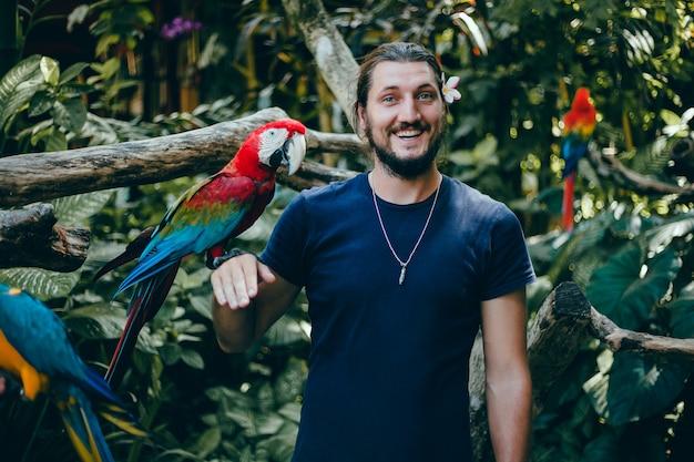Chico joven posando en un zoológico con un loro en la mano, un hombre barbudo y un pájaro