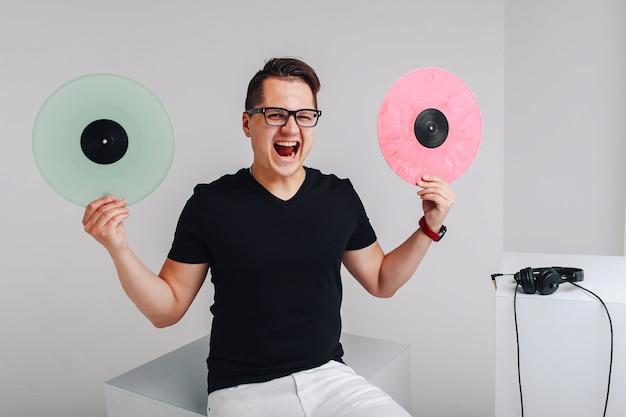 Chico joven positivo con discos de vinilo. joven inconformista tiene discos de vinilo en sus manos.