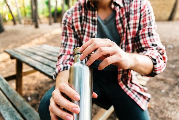 Chico joven en el prado con termo botella de plata en aluminio.
