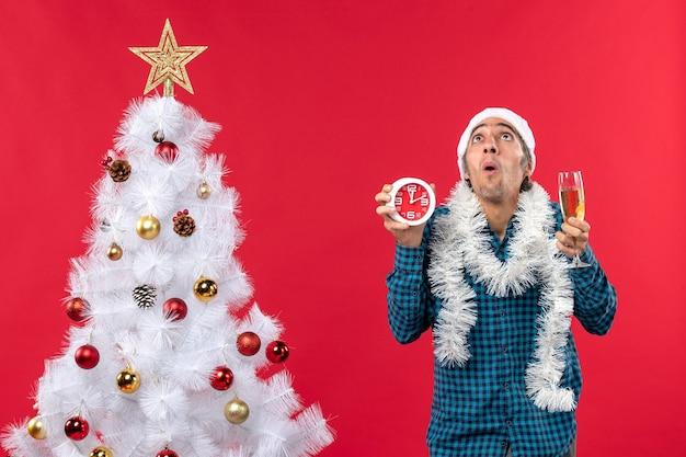 Chico joven preocupado con sombrero de santa claus y sosteniendo una copa de vino y reloj de pie cerca del árbol de navidad