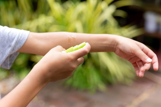 Chico joven rocía repelente de insectos contra picaduras de mosquitos en su brazo
