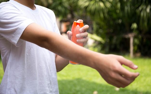 Chico joven rocía repelentes de insectos en la piel con botella de spray