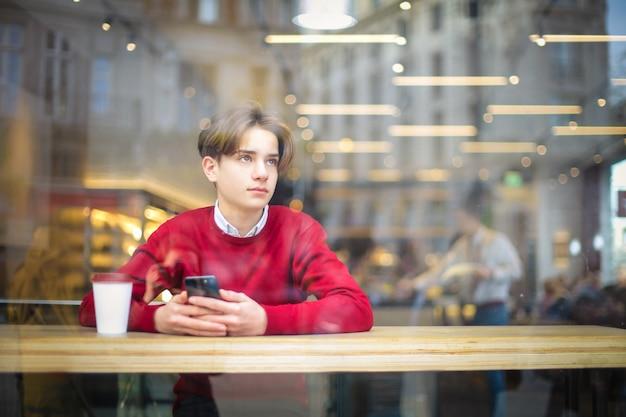 Chico joven sentado en una cafetería, tomando un café