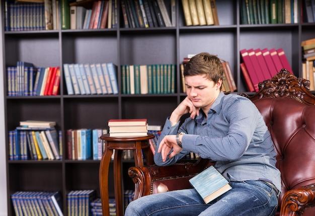 Chico joven serio en moda de moda sentado y esperando en la silla de la biblioteca con un libro, mirando su reloj de pulsera