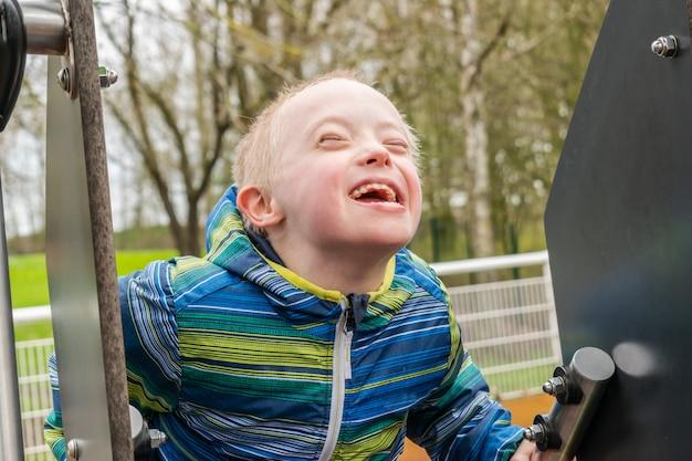 Chico joven con síndrome de down que juega en un patio de recreo