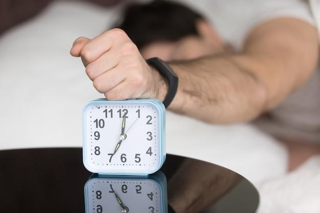 Chico joven soñoliento enojado apagando ruidoso molesto reloj despertador