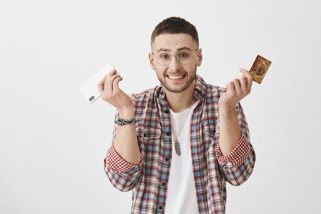 Chico joven sorprendido con gafas posando con su teléfono y tarjeta