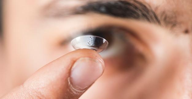 Chico joven sosteniendo una lente en su dedo