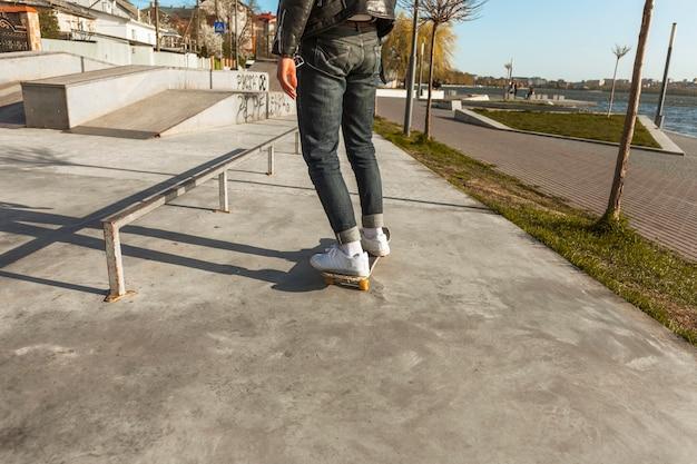 Chico joven con su monopatin en la pista de skate