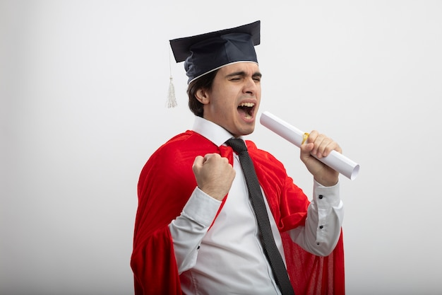 Chico joven superhéroe alegre con corbata y sombrero graduado con diploma y canta mostrando gesto de sí