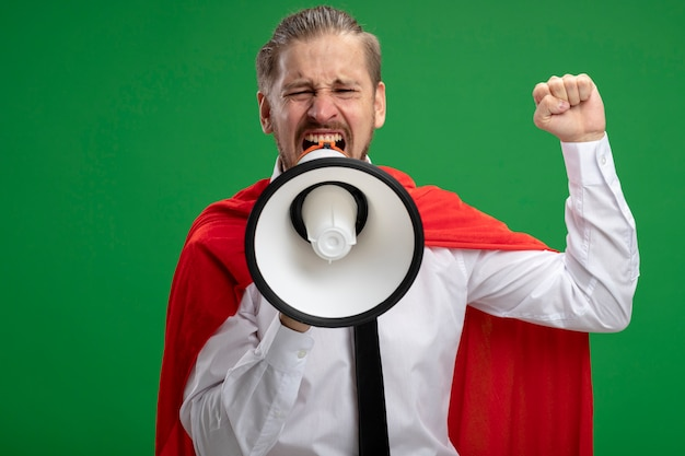 Chico joven superhéroe alegre habla en altavoces y levantando el puño aislado sobre fondo verde