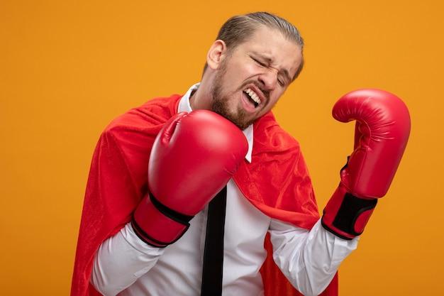 Chico joven superhéroe cansado con corbata y guantes de boxeo aislados sobre fondo naranja