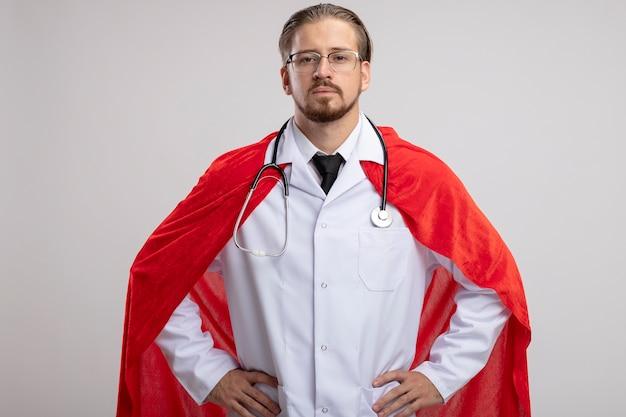 Chico joven superhéroe confiado con bata médica con estetoscopio y gafas poniendo las manos en la cadera aislado sobre fondo blanco.