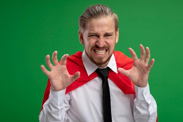 Chico joven superhéroe enojado mostrando gesto de estilo tigre aislado en verde