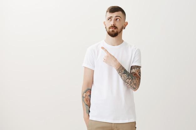 Chico joven vacilante con tatuajes apuntando y mirando la esquina superior izquierda dudoso