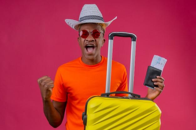 Chico joven viajero afroamericano con camiseta naranja y sombrero de verano con maleta de viaje y boletos de avión gritando loco y enojado con expresión enojada apretando el puño sobre fondo rosa