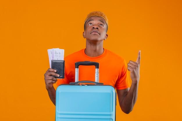 Chico joven viajero con camiseta naranja con billetes de avión y maleta mirando hacia arriba apuntando a algo con cara seria de pie sobre la pared naranja