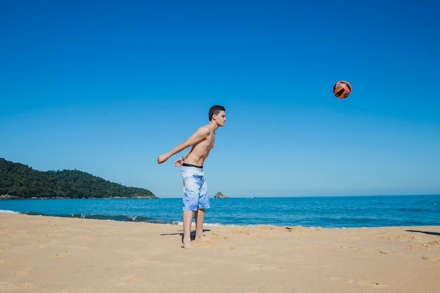 Chico jugando al voleibol en la playa