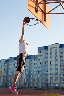 Un chico jugando baloncesto en el campo de deportes.