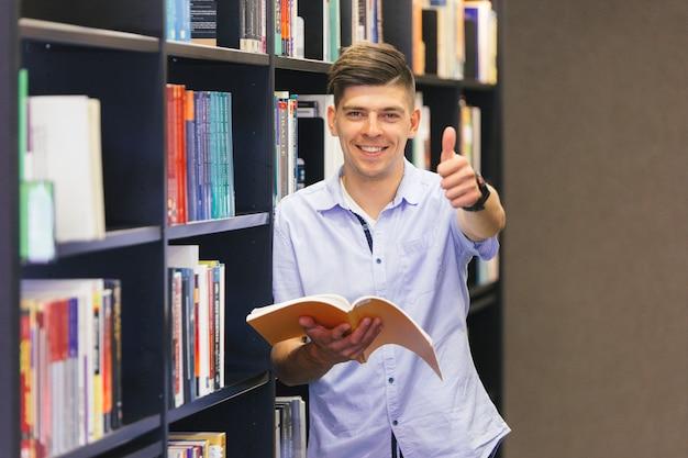 Chico con libro haciendo pulgar arriba gesto