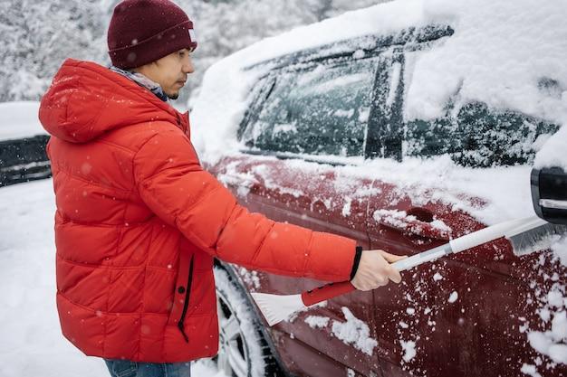 El chico limpia el coche de la nieve con un cepillo.