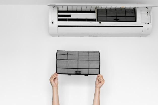 El chico limpia el filtro del aire acondicionado del hogar del polvo.