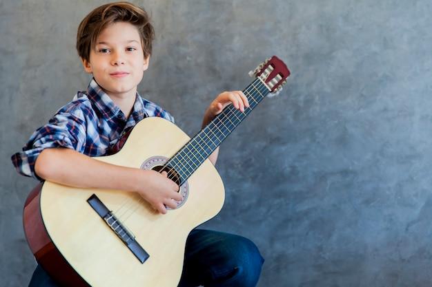 Chico lindo adolescente con guitarra