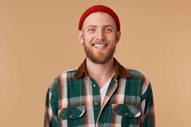 Chico lindo alegre con barba vestido con una camisa y sombrero rojo está sonriendo afablemente