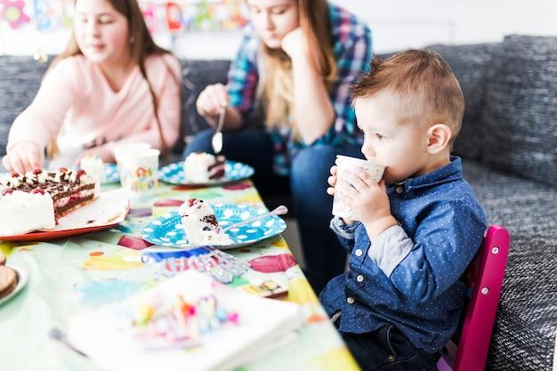 Chico lindo bebiendo y comiendo pastel