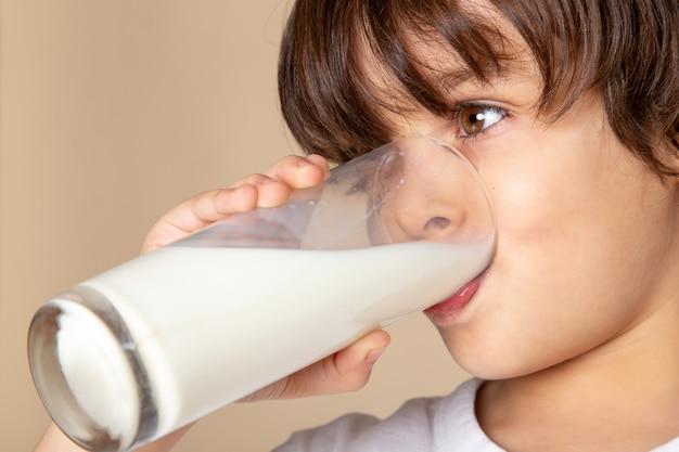 Chico lindo bebiendo leche entera blanca