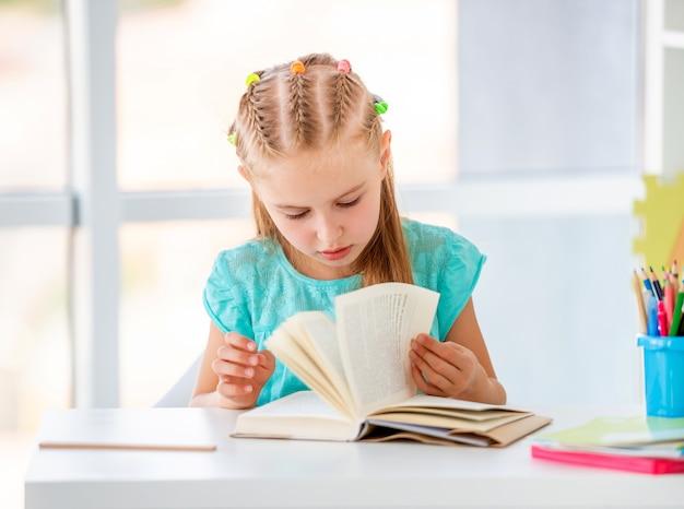 Chico lindo chica encantadora lectura en la mesa