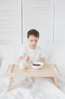 Chico lindo comiendo bolas de chocolate desayuno sentado en la cama con sábanas blancas