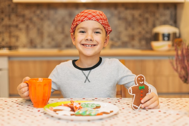 Chico lindo comiendo galletas de hombre de jengibre