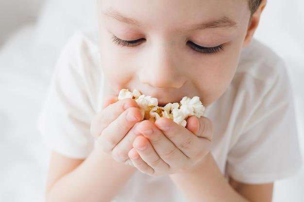 Chico lindo comiendo palomitas de maíz sentado en la cama con sábanas blancas