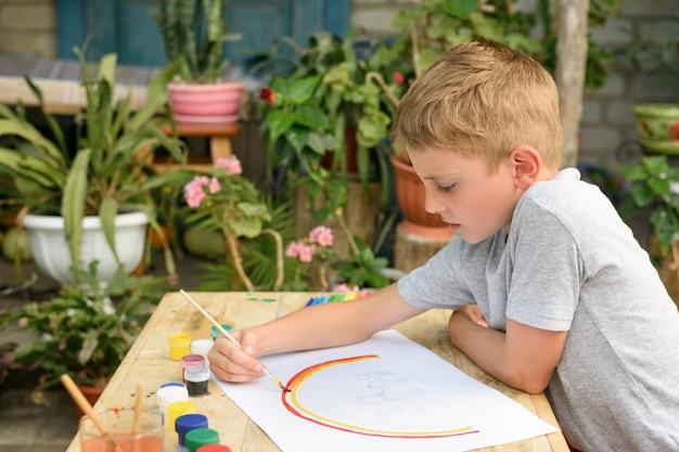 Chico lindo dibuja un arco iris en un papel