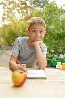 Chico lindo dibuja con lápices bodegones. aire libre. jardín al fondo. concepto creativo