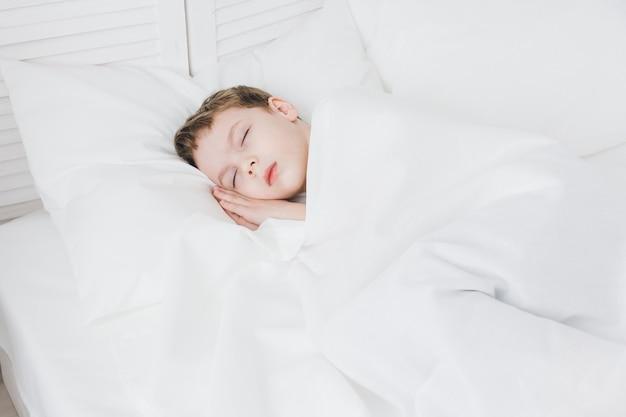 Chico lindo duerme en la mañana en la cama