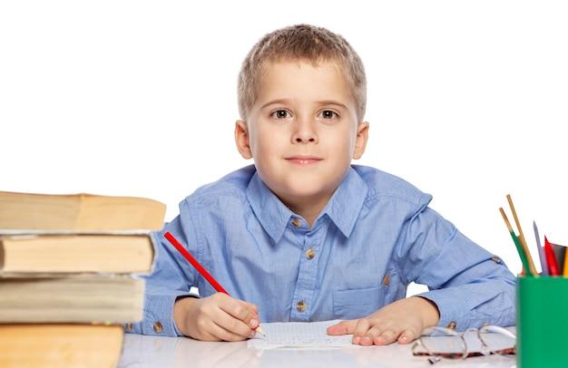 Chico lindo de edad escolar haciendo los deberes en la mesa. es interesante aprender aislado en un fondo blanco.