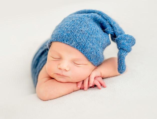 Chico lindo en gorro azul durmiendo