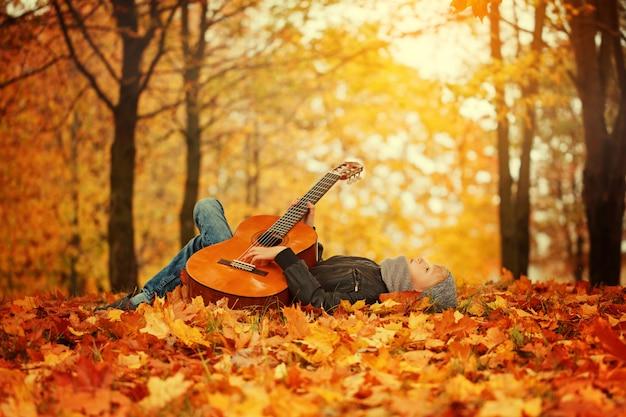 Chico lindo con guitarra, tirado en el pasto en día soleado de otoño