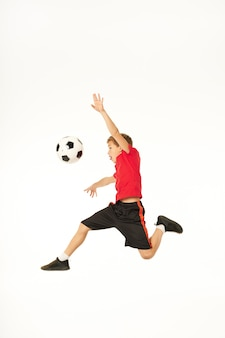 Chico lindo jugador de fútbol mirando una pelota de fútbol y sacando la lengua mientras salta en el aire. aislado sobre fondo blanco