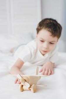 Chico lindo jugando con avión de madera sentado en la cama