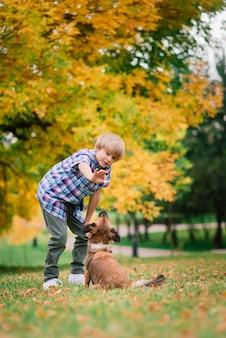 Chico lindo jugando y caminando con su perro en la pradera.