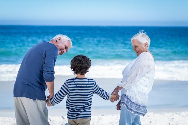 Chico lindo de la mano de sus abuelos