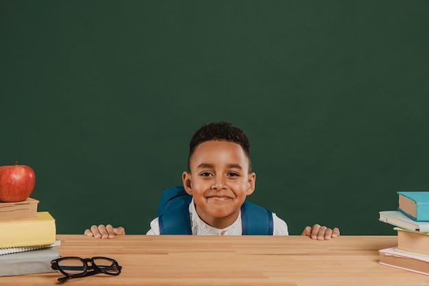 Chico lindo con mochila escondido detrás de la mesa