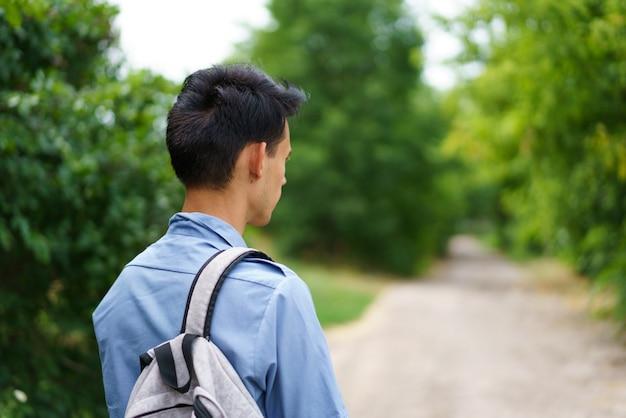 Chico lindo con una mochila de pie en la carretera en el campo joven caucásico con camisa azul viaja h ...